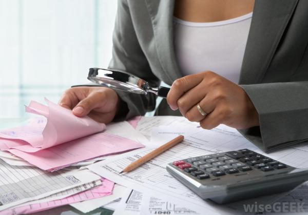woman-in-suit-with-magnifying-glass-near-calculator