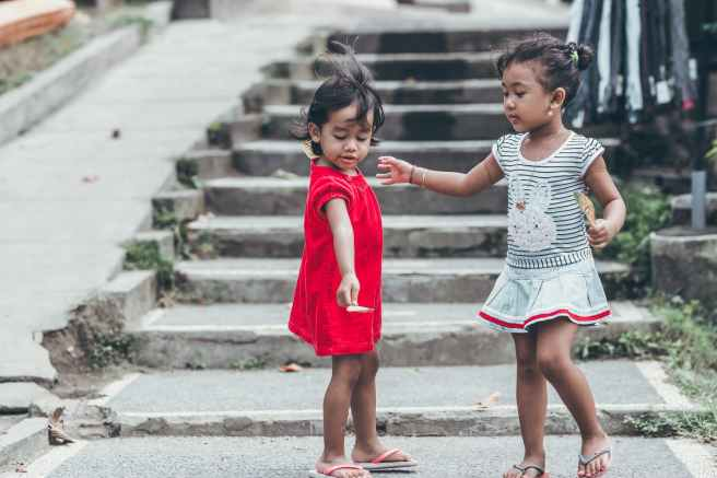 two toddler wearing red and gray dresses