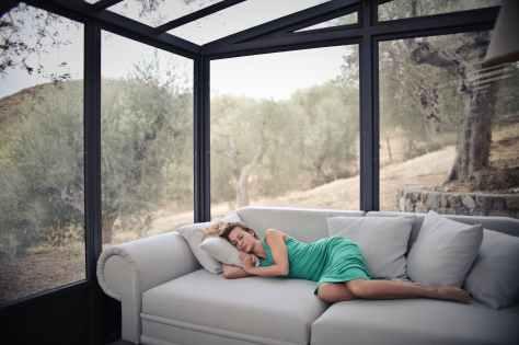 woman sleeping on sofa with throw pillows