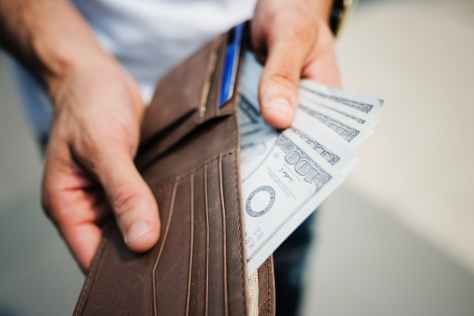 man holding brown leather bi fold wallet with money in it